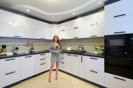 Young woman at luxury modern white kitchen interior in modern style 스톡 콘텐츠