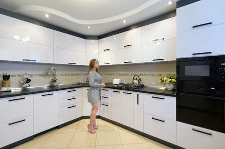 Young woman at modern white kitchen interior 스톡 콘텐츠