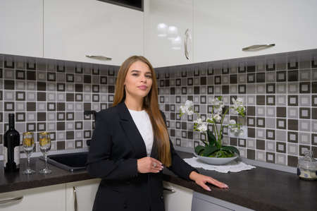 Young woman at luxury modern black and white kitchen interior in provence style