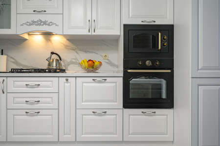White kitchen in classic style, front view