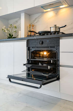 Open electric oven at white kitchen