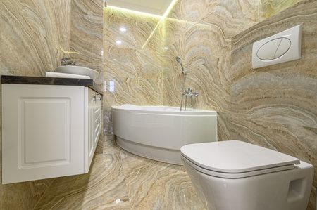 Luxury bathroom with white bathub and beige marble tiles