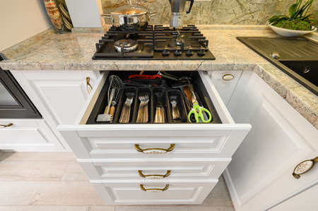 Drawers pulled out at modern classic white kitchen furniture