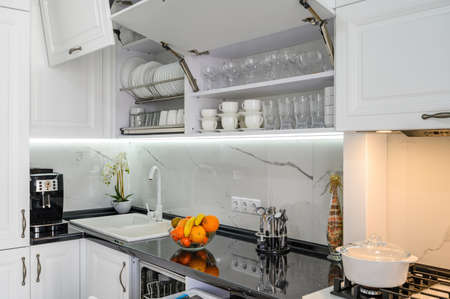 Luxurious white modern kitchen interior, drawers pulled out, doors open Banque d'images