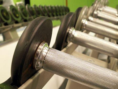 fitnesscenter: Row of bar bells reflected in mirror.
