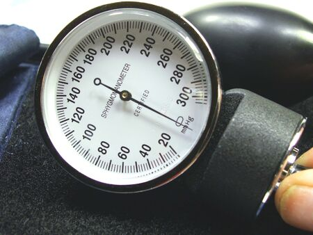 diastolic: Blood pressure cuff with hand holding pressure meter all isolated on white. Stock Photo