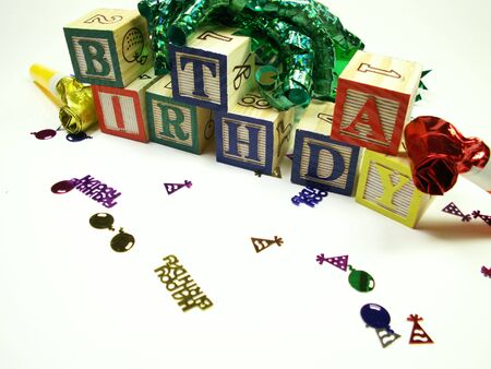 Childs blocks spelling birthday isolated on white. Blocks surrounded by ribbon, noise makers and confetti. photo