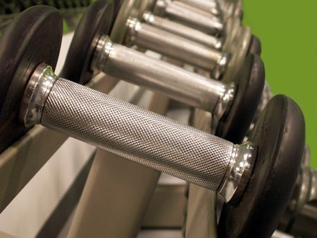 fitnesscenter: Row of bar bells in varying weights lined up in a row.