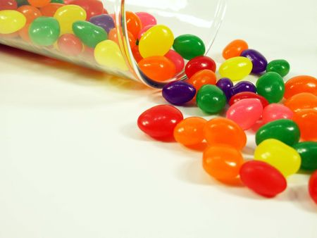 falling out: Jelly beans falling out of a glass jar isolated on white.