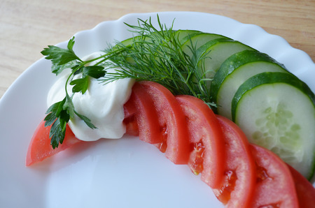 breakfeast: Tomato and cucumber on white plate