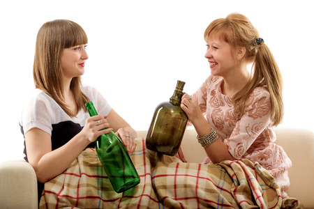 Two girls on a sofa after drinking wine, isolated photo