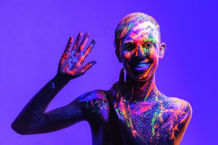 Man covered with fluorescent paint on color background