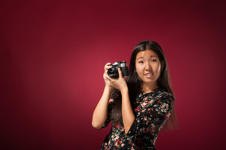 specialize: Oriental girl posing in studio with old camera Stock Photo