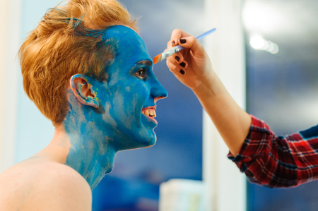 bod: Young man preparing for photosession with bodyart painting in studio, backstage