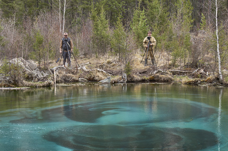 ulagan: Two photographers taking pictures near a geyser lake in Altai Stock Photo