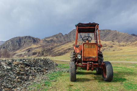 old tractor: Lonely old tractor in Altai steppe in rainy day Stock Photo