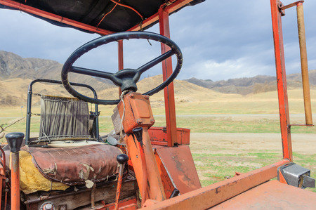 outworn: Lonely old tractor in Altai steppe in rainy day Stock Photo
