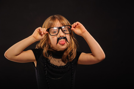 affecting: Young girl at Halloween party with spectacles and fake mustache