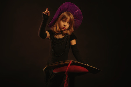 affecting: Young girl at Halloween party with hat and book