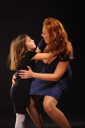 kiss love: Young girl and mature mother embracing on black background