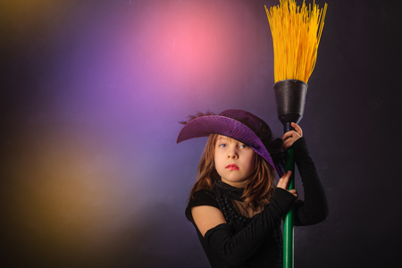 affecting: Young girl at Halloween party with hat and broom