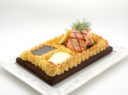 nourish: Grilled salmon on the bead of mashed potatoes isolated on white