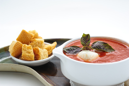 epicure: Tomatoe soup with mozarella cheese studio shot Stock Photo