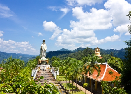 White Guan yin and Golden Buddha among green hill, South of Thailand photo