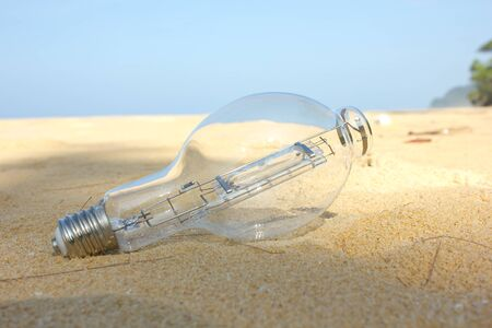 Lightbulb of the lighthouse on beach photo