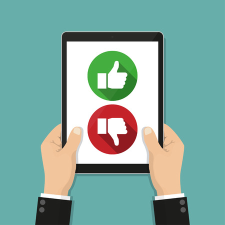 Website rating feedback and review concept. Hand holding tablet with like and dislike Banco de Imagens - 74769820