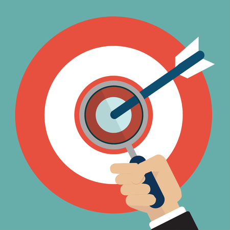 Businessman hand with magnifying glass on target with arrow