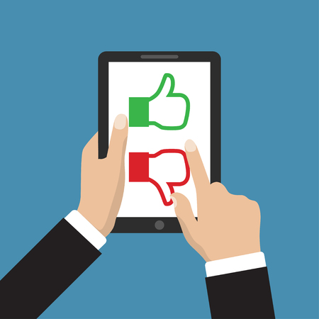 evaluate: Website rating feedback and review concept. Hand holding and pointing to a tablet with like and dislike hand sign button on the screen