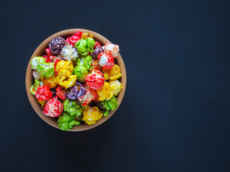 Colored popcorn in a bowl on a dark background.