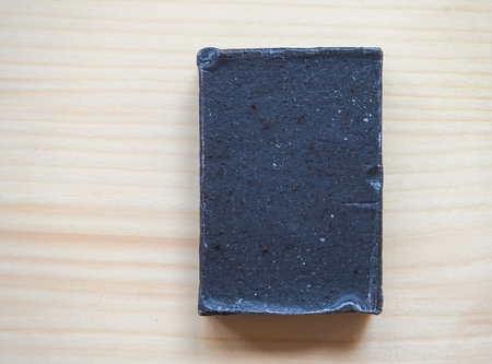 Handmade black carbon soap on wooden background. Stock Photo