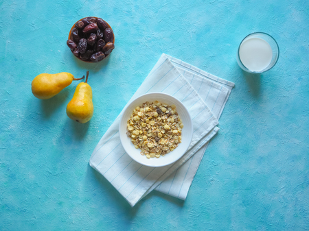 Healthy muesli with dates and fresh pears on blue background. Archivio Fotografico
