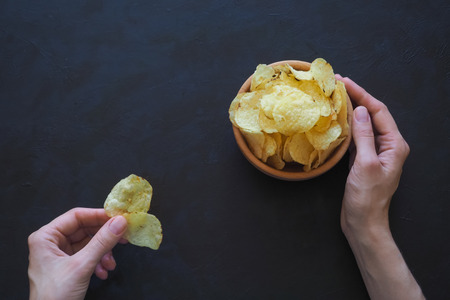Womans hands holding potato chips on a dark background.