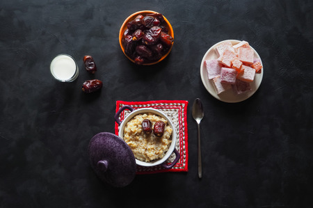Simple healthy food. Oatmeal with dates and milk on the black table. Stock Photo