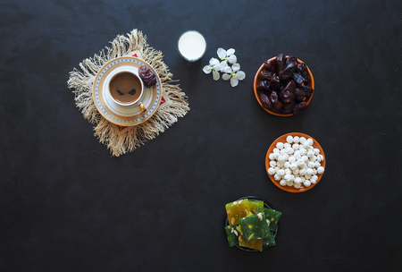 Black coffee, milk, dates and Turkish sweets on a black background. Sweet food for Ramadan.