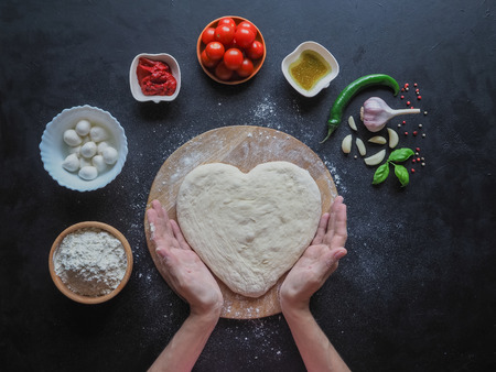 Heart-shaped dough and a set of ingredients for pizza on a black table. The view from the top