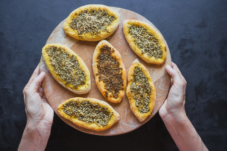 Scones with zatar. Manakish Arabic on a wooden chopping board on a black table