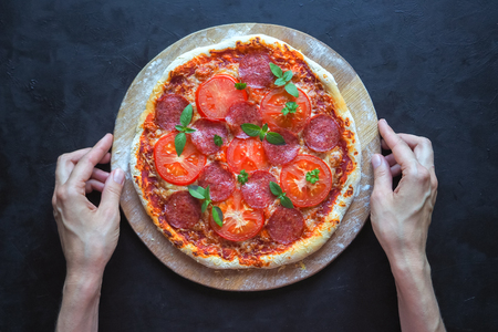 Home-made pepperoni pizza on a black table Stock Photo
