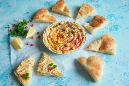 Traditional Middle east appetizer Hummus served with fresh pita bread and herbs.