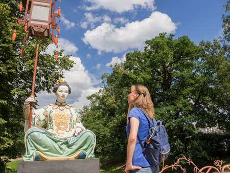 The tourist looks at the ancient Chinese statues on the Big Chinese Bridge in Tsarskoye Selo. Russia.