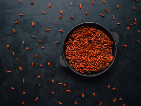 Goji berries in a pan on a black wooden table background