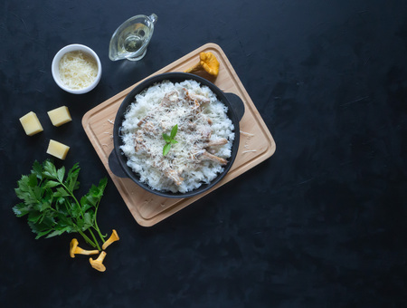 Risotto of chanterelles in a cast iron pan on a black table