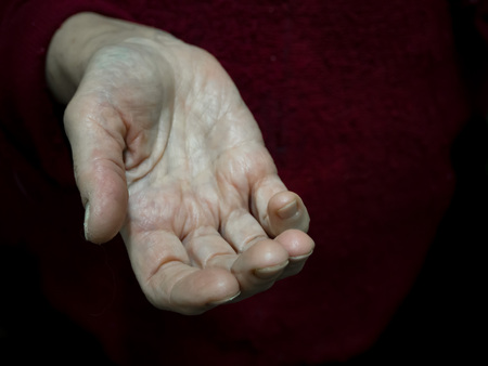 Begging alms by the hand of the pensioner Archivio Fotografico