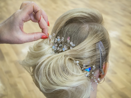Hair stylist makes the bride a wedding hairstyle with hair detail accessory, closeup rear view