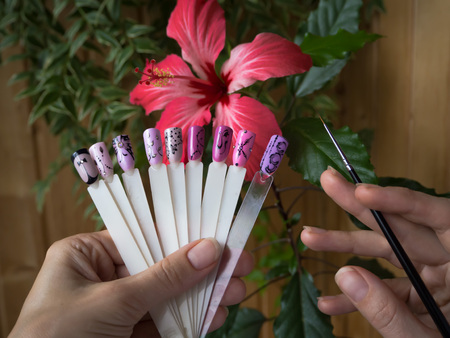 Nail design, the choice of pattern tips. Painted tips on the background of a red flower 版權商用圖片