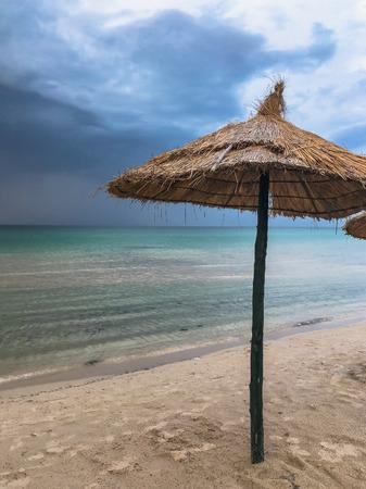 Dramatic landscape with beach umbrellas on the sea