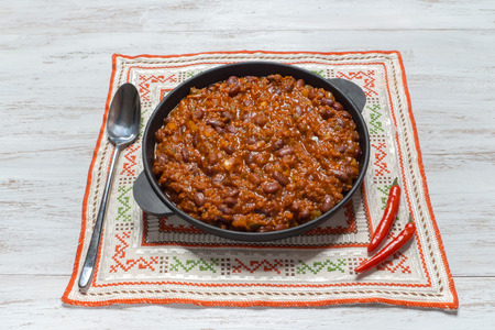 Mexican chili. Chili con carne in frying pan on white wooden background